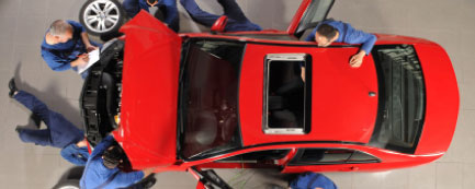 mechanics working on red sports car